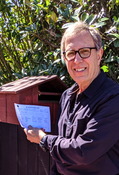 Steve ZL2KE by his letterbox holding a radiogram he received