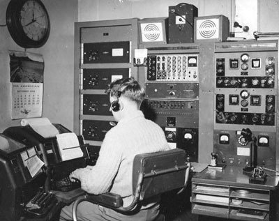 Aviation radio operator Andy Bennie in the tower at Musick Point, c1959